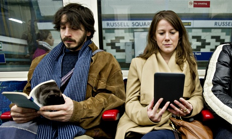 Woman reading an e-book on a tube train in London