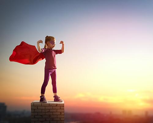 Little child girl plays superhero. Child on the background of su