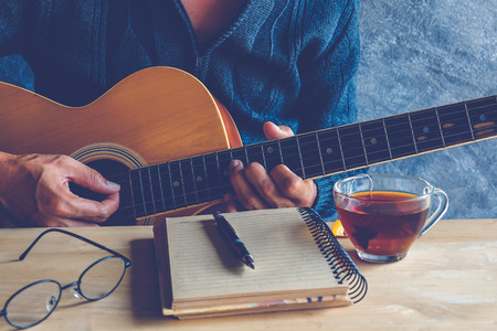 69465831 - young man composing the song with guitar on table with tea cup